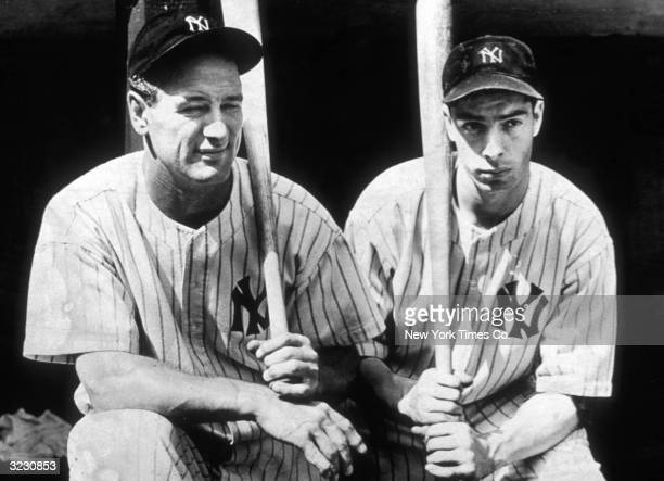 Portrait of American baseball players Lou Gehrig and Joe DiMaggio both of the New York Yankees kneeling with their baseball bats in uniform