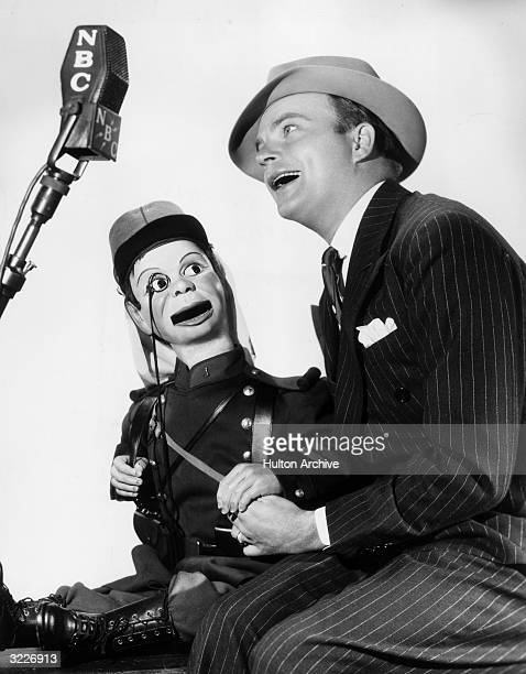 Portrait of American ventriloquist Edgar Bergen and his dummy Charlie McCarthy singing in front of an NBC microphone Bergen is wearing a pin stripe...