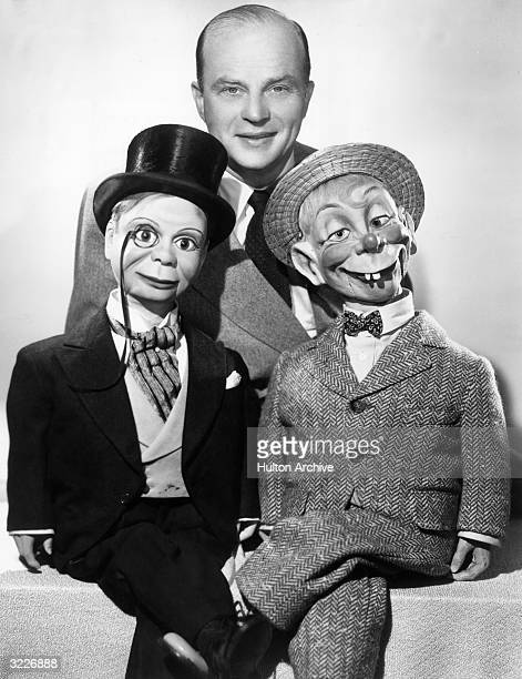 Portrait of American ventriloquist Edgar Bergen standing in a suit behind his two dummies Charlie McCarthy and Mortimer Snerd Charlie McCarthy is...