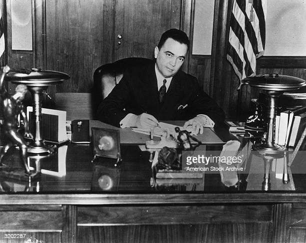 Portrait of FBI director J. Edgar Hoover sitting at a desk while signing a document.