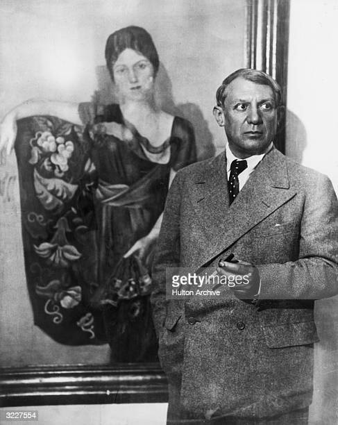 Portrait of Spanish painter Pablo Picasso smoking a cigarette with a filter standing in front of his 1917 painting of his first wife Olga Picasso is...