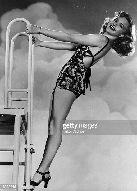 Priscilla Lane the film actress balancing at the top of the diving board in typical 'pinup' pose