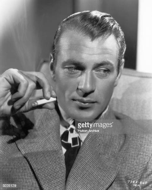Promotional headshot portrait of American actor Gary Cooper looking to his side while holding a smoking cigarette.