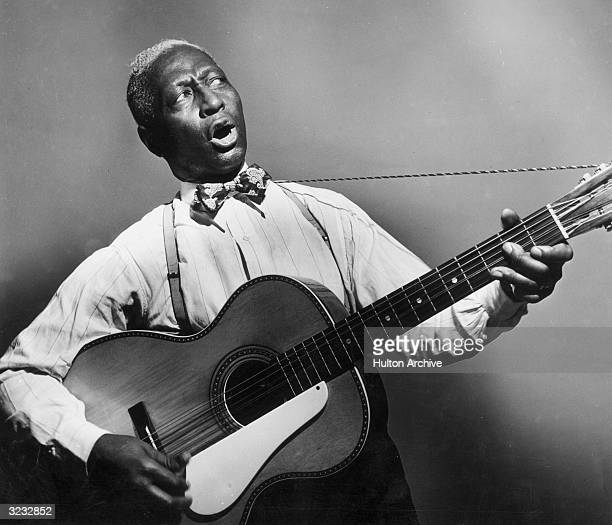 Promotional portrait of American blues musician Huddie 'Leadbelly' Ledbetter playing a 12-string guitar and singing.