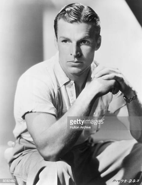 Promotional studio portrait of American actor Buster Crabbe seated with his elbows propped on his knees Crabbe was a former Olympic swimmer