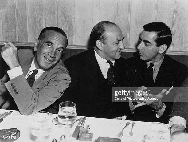Russianborn American singer Al Jolson with Harry Cohn and American film actor Eddie Cantor having dinner at a restaurant