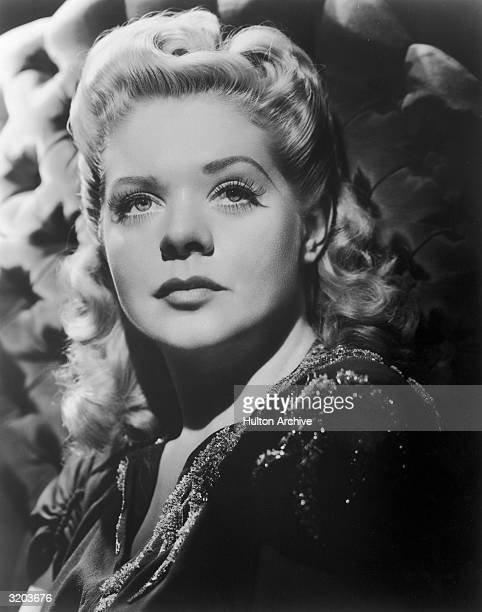 Studio headshot portrait of American singer and actor Alice Faye wearing a beaded blouse posing in front of a quilted headboard