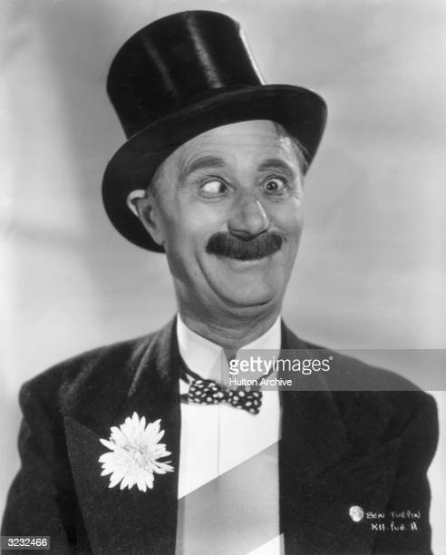 Studio headshot portrait of crosseyed American comedian Ben Turpin wearing a top hat tails with a flower in his lapel a polkadotted bow tie and a sash