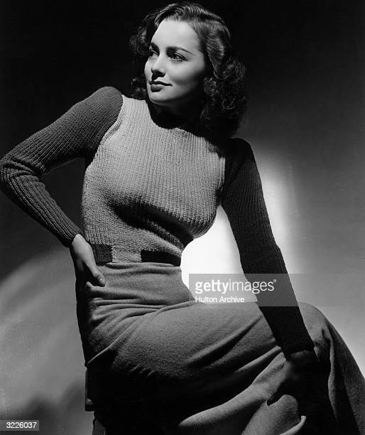 Studio portrait of British-born actor Olivia de Havilland sitting on a stool and looking over her shoulder as she rests her hand on her hip. De...