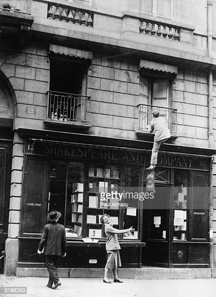 Sylvia Beach unofficial historian of 'The Lost Generation' watches composer George Antheil climbing up to a second floor window of her bookshop...