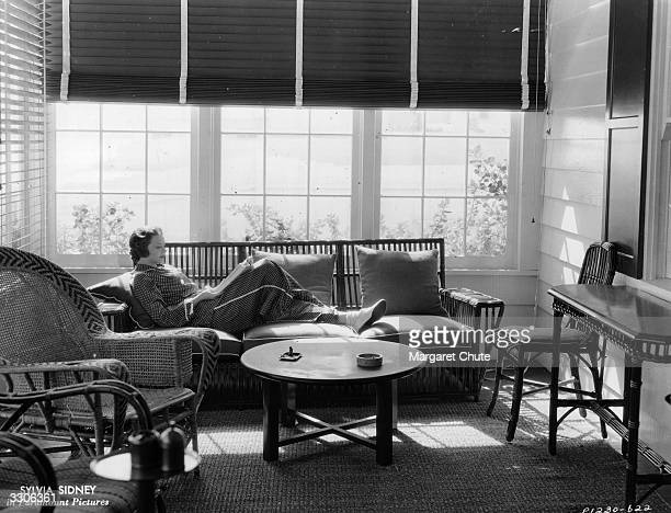 Sylvia Sidney , dark haired leading lady of the 1930's, reading in her beach Malibu home.