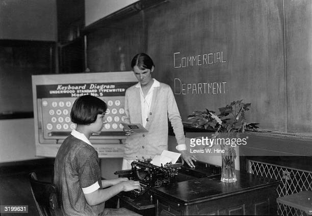 Teacher dictates to a young female pupil in a typing lesson A large diagram of the typewriter's keyboard stands in the background