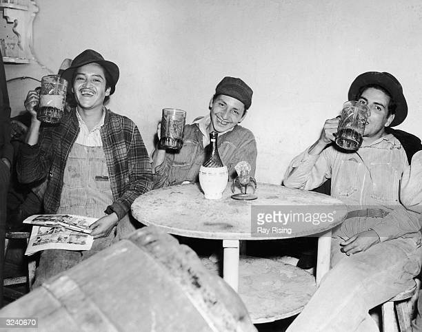 Three farm workers raise their mugs of beer as they sit together at a table Mexico