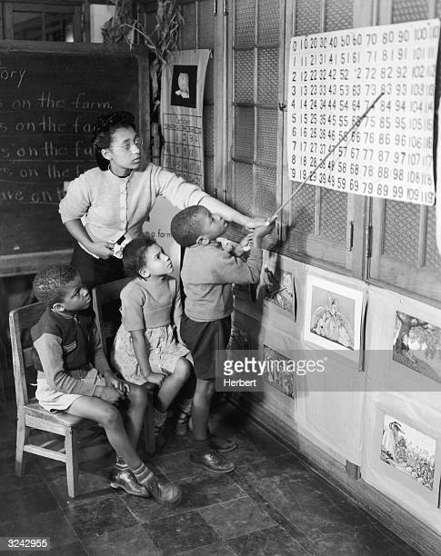 Three young AfricanAmerican students learn mathematics skills from a teacher at the Hampton Institute an AfricanAmerican university located in...