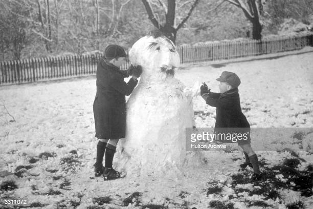 Two children making a snowman complete with 'hair' in Finsbury Park London