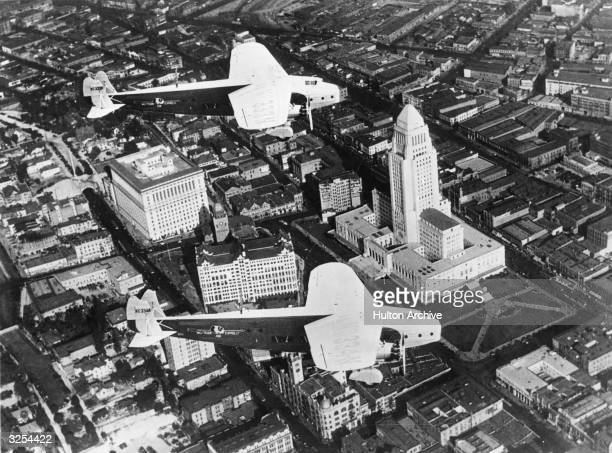 Two Fokker monoplanes in flight over downtown Los Angeles California Los Angeles City Hall is on the right