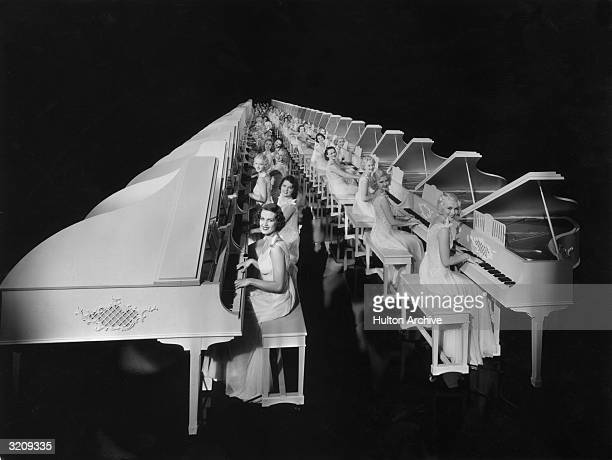 Two rows of chorus girls in white dresses sit at two rows of white pianos in a still from a Gold Diggers film