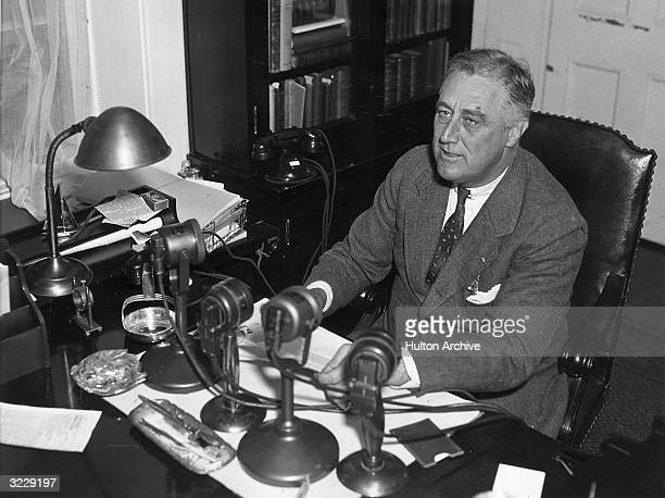 US president Franklin Delano Roosevelt speaks into four radio microphones which sit on his desk during one of his live nationwide 'fireside chat'...