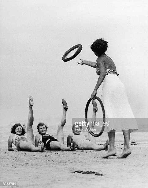 Women bathers play a ringtoss game with rubber bicycle tires Three women lay on the beach and raise their legs while the other tosses the tires