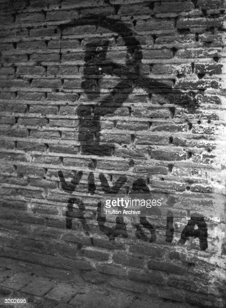 A hammer and sickle are painted on a brick wall somewhere in Spain Spanish Civil War The caption below reads 'Viva Rusia'