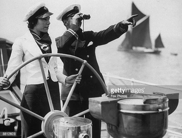 Passenger on the London to Clacton steamer takes a turn at the wheel under the watchful eye of the officer.