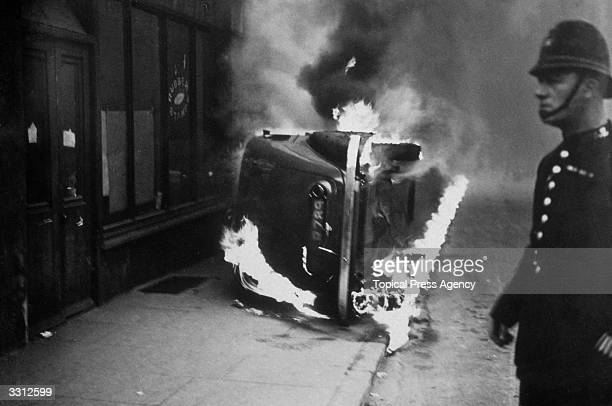 A policeman stands by a burning car set alight during a communist march in the East End of London