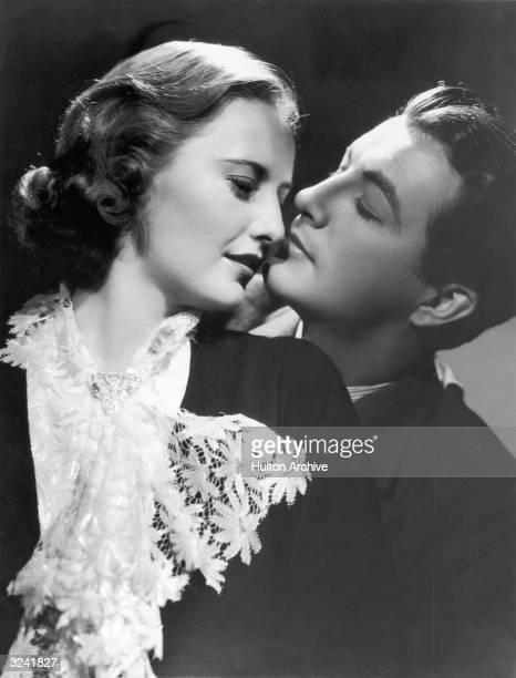 American actor Barbara Stanwyck wearing a blouse with a lace bib looks back while leaning against American actor Robert Taylor in a promotional...