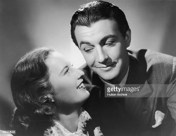American actors Barbara Stanwyck and Robert Taylor smile while facing each other in a promotional studio portrait They married in 1939