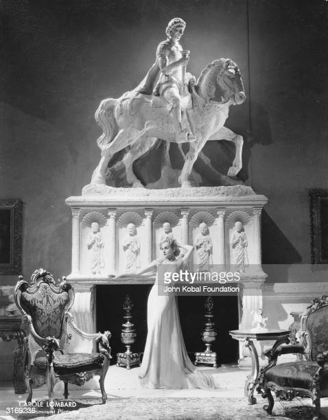 American film actress Carole Lombard poses against a massive fireplace surmounted with a carved horse and rider