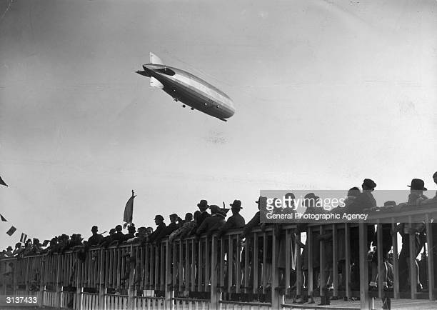 Berliners watch the rigid airship the Graf Zeppelin circles the Tempelhof Aerodrome after successfully flying around the world