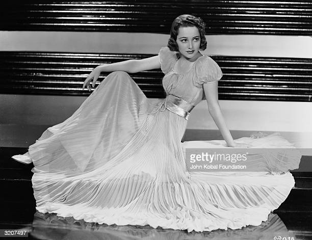Britishborn actress Olivia de Havilland wearing a fulllength pleated gown with a gathered waist and puffed sleeves