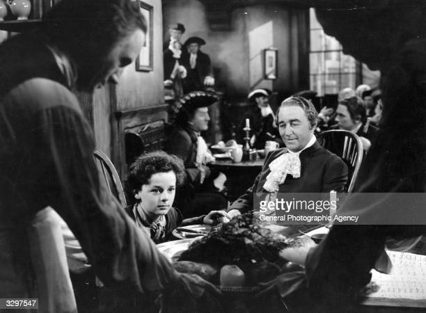 Freddie Bartholomew the British child actor is being offered a job by Sir Guy Standing the British stage actor in a scene from 'Lloyd's Of London'...
