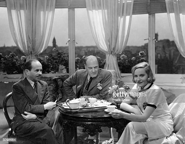 German actress Elisabeth Bergner taking tea with her husband Hungarian director Paul Czinner and Max Schach on the set of 'Dreaming Lips' at the...