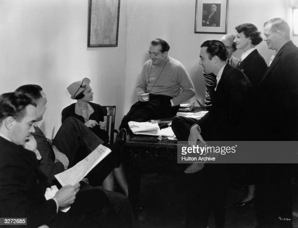 German Director Fritz Lang is laughing and drinking coffee between scenes. Sylvia Sidney would love a cup but her physician has restricted her to one...