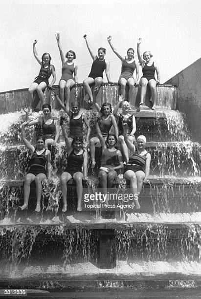 Schoolgirls sitting in the waterfall at Finchley swimming pool London