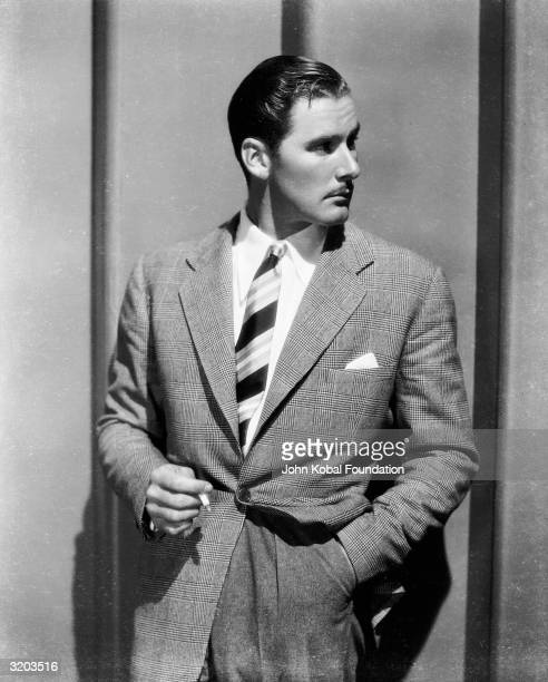 Tasmanian film star Errol Flynn wearing a jacket and tie and smoking a cigarette