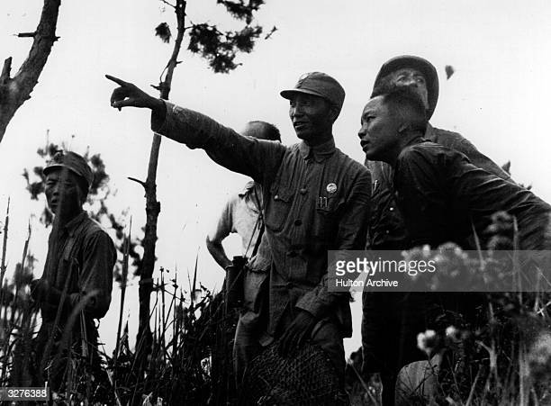 A Chinese artillery commander points out a target to three correspondents on the Yangtze front of Yeman during the SinoJapanese conflict