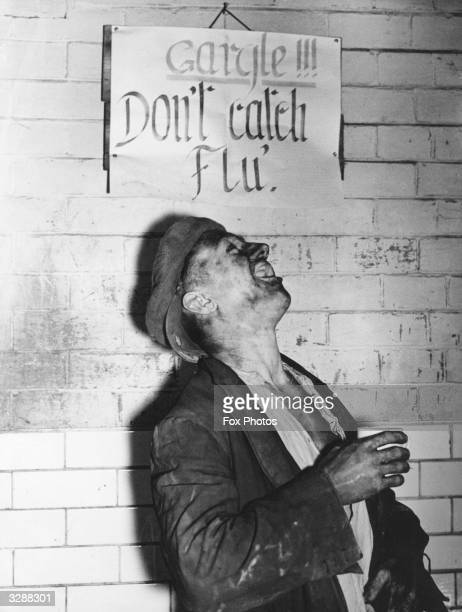 A miner at the Houghton Main Colliery Yorkshire has an antiflu gargle after work in front of a notice that advises him to do so to avoid the serious...