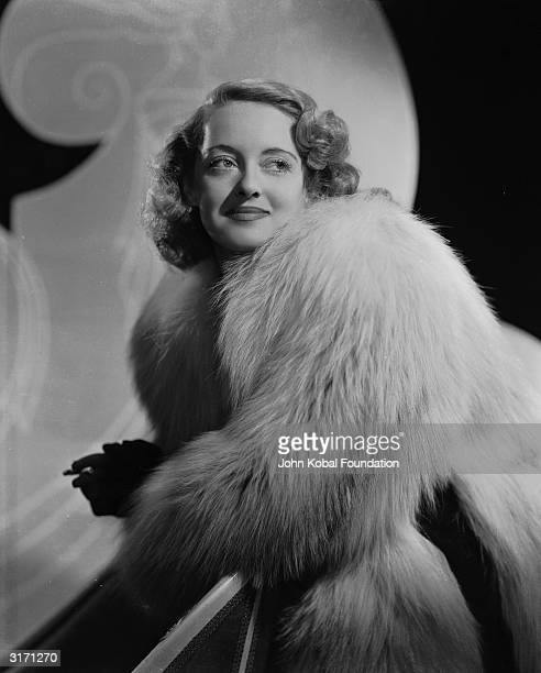 American actress Bette Davis in a deep pile fur coat