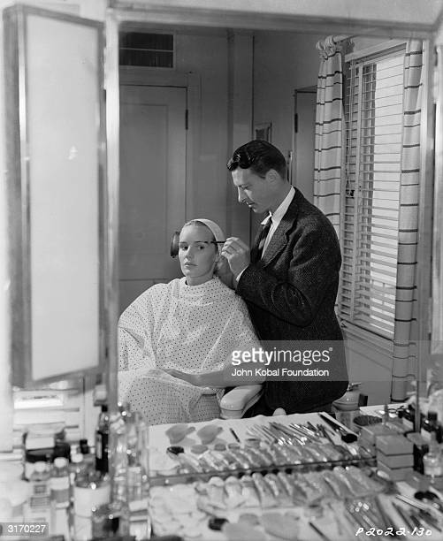 American actress Frances Farmer having her makeup done by a professional