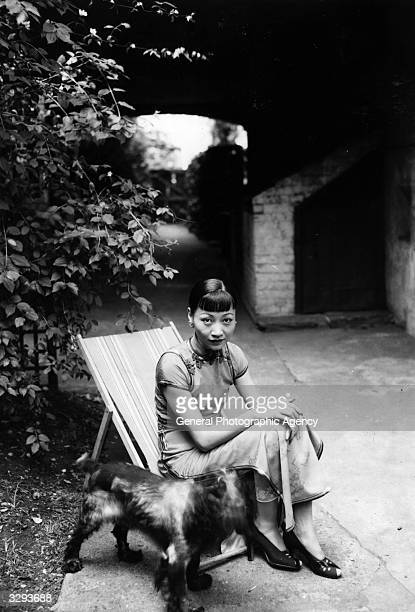 Anna May Wong born Wong Liu Tsong in the garden with her dog