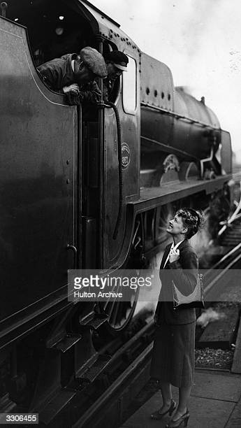 Ellen Drew the screen name of Terry Ray the Hollywood film actress talks to the engine driver and fireman of her train at Waterloo station