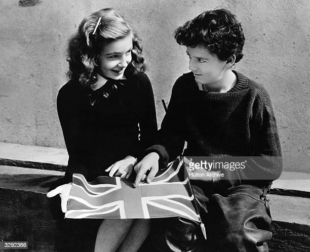 Freddie Bartholomew the child actor explains to co child actress Joan Brodel at the MGM studios what the integral parts of the Union Jack flag are