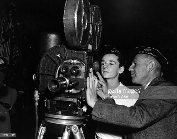 Freddie Bartholomew the Hollywood child actor is shown the integral parts of a movie camera by Sam Greenwald a newsreel cameraman