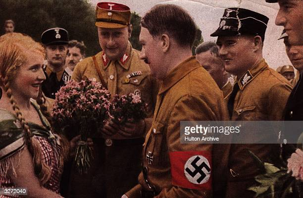 German dictator Adolf Hitler wearing swastika armband on his brown shirt meets an adoring young female follower