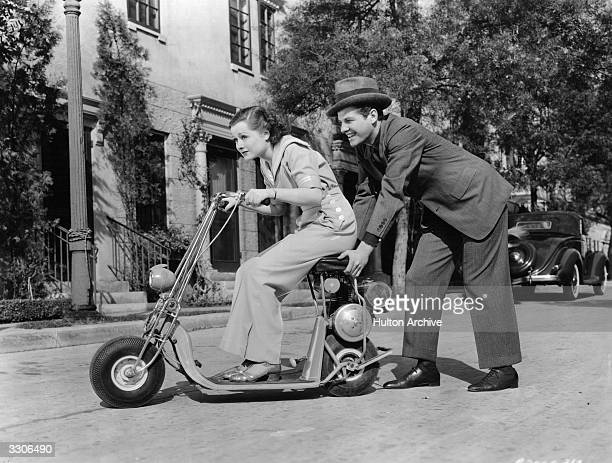 Hollywood actress Eleanore Whitney gets a push from actor Robert Cummins on the Motorglyde the first motorised scooter