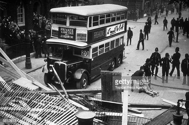 Policemen clearing a barricade erected by antifascists during a Fascist demonstration in South East London The policemen arrived in a bus bearing the...