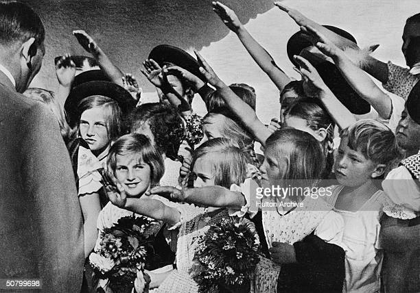 The hands of children greeting the German Nazi dictator Adolf Hitler author of Mein Kampf