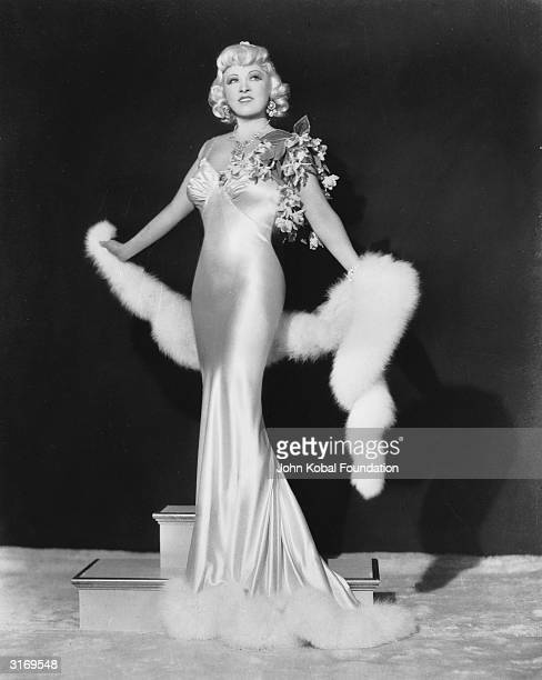 The original Hollywood sex symbol, Mae West wearing a figure hugging satin dress with a fur stole.