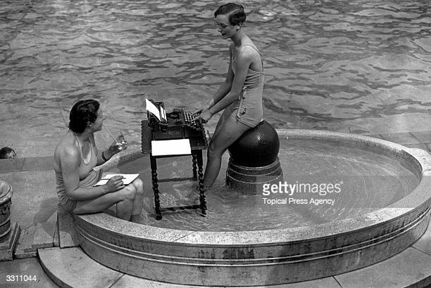 Two city typists at work in an open air swimming pool during a hot summer